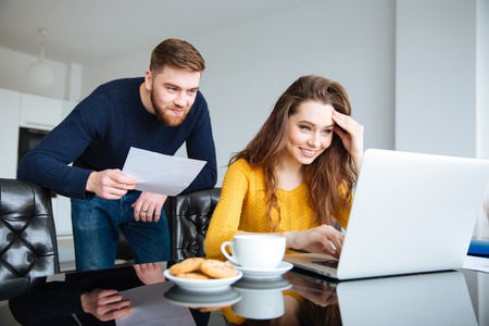 Photo for Portrait of a happy young couple calculating bills at home - Royalty Free Image