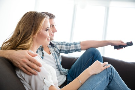Photo pour Profile of happy couple sitting on couch and watching tv together - image libre de droit