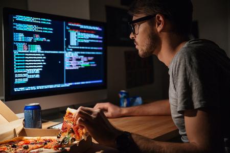 Foto de Profile of concentrated young software developer eating pizza and coding at home - Imagen libre de derechos