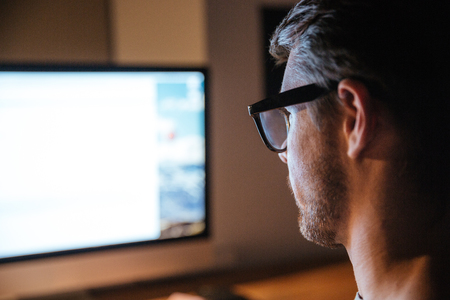 Foto de Concentrated bristled young man in glasses sitting and looking at screen of monitor - Imagen libre de derechos