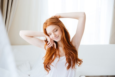 Foto de Sensual smiling redhead young woman with long hair sitting and stretching in bed - Imagen libre de derechos