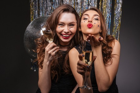 Cheerful beautiful young women having party and sending kiss over black background