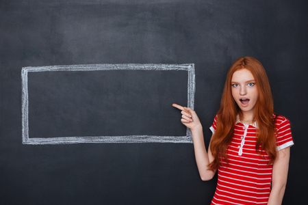 Photo pour Amazed cute redhead woman pointing on copyspace inside frame drawn on blackboard background - image libre de droit