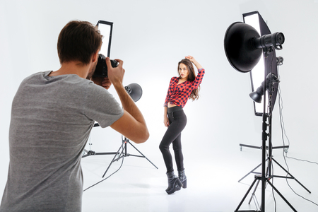 Foto de Photographer working with model in equipped studio - Imagen libre de derechos