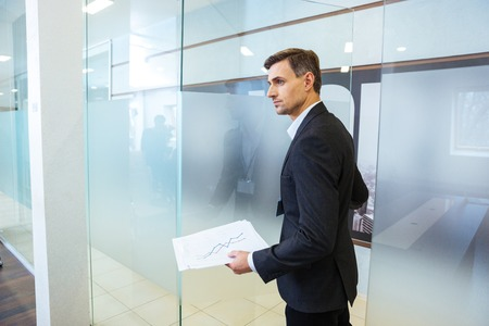 Confident businessman in formalwear holding documents and entering the office