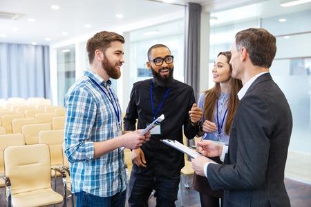 Foto de Multiethnic groop of inspired young people standing and discussing new project in conference room - Imagen libre de derechos