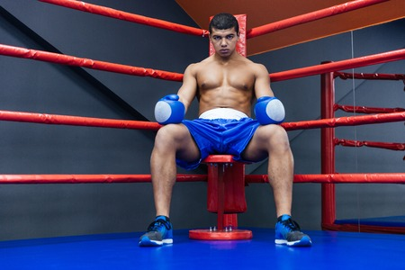 Photo pour Professional male boxer sitting in the corner of the boxing ring - image libre de droit