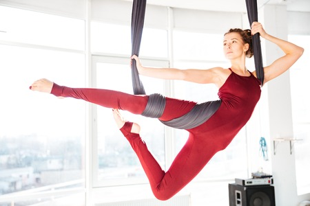 Serious attractive young woman doing antigravity yoga using hammock in studio