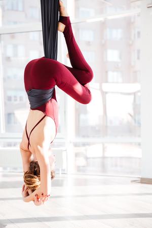 Photo pour Back view of young woman practicing antigravity yoga exercises in studio - image libre de droit