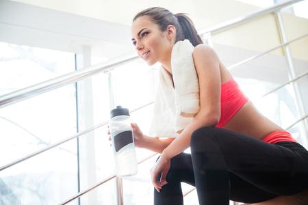 Foto de Happy beautiful young sportswoman resting and drinking water on stairs in gym - Imagen libre de derechos