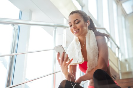 Foto de Cheerful beautiful young woman sitting on stairs in gym and listening to music - Imagen libre de derechos