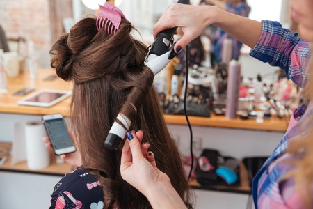 Photo for Woman hairdresser making hairstyle using curling iron for long hair of young female with smartphone in beauty salon - Royalty Free Image