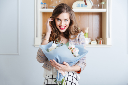 Photo for Portrait of happy cute young woman with bouquet of flowers in cafe - Royalty Free Image