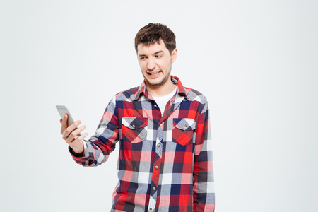 Man with disgust emotion holding smartphone isolated on a white background