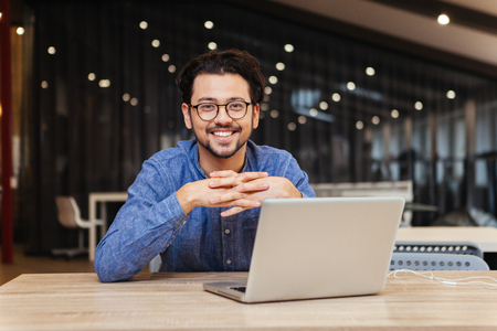 Smiling man using laptop computer in office and looking at camera