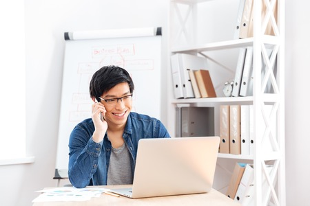 Foto de Happy handsome young businessman in glasses using laptop and talking on cell phone in office - Imagen libre de derechos
