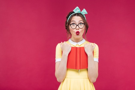 Foto de Charming surprised pinup girl in glasses standing and holding red book over pink background - Imagen libre de derechos
