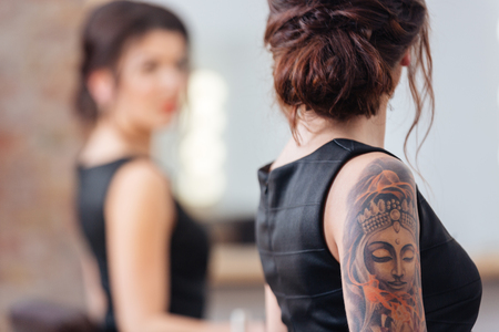 Foto de Back view of pretty young woman in black dress with tattoo on her hand standing in front of the mirror - Imagen libre de derechos