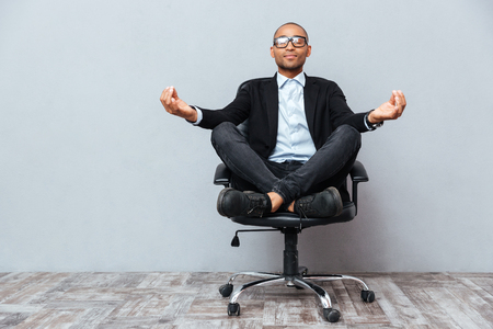 Photo pour Relaxed handsome african young man sitting and meditating on office chair - image libre de droit