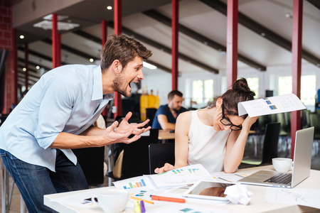 Photo for Mad crazy young businessman arguing with sad stressed businesswoman at work in office - Royalty Free Image