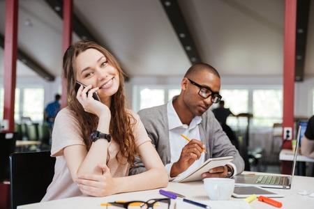 Photo for Cheerful beautiful young business woman talking on cell phone and working with serious african man in office - Royalty Free Image