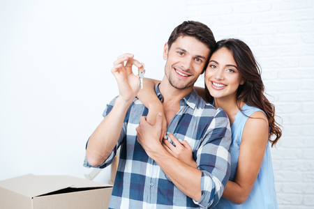 Young smiling couple showing keys to new home hugging looking at cameraの写真素材