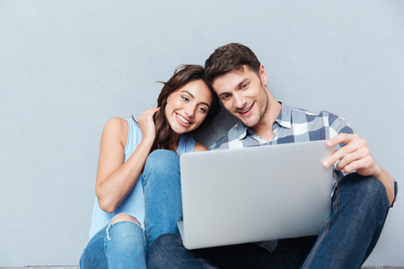 Photo for Portrait of happy young couple using laptop isolated on gray background - Royalty Free Image