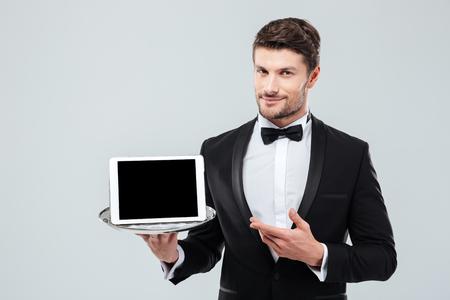 Foto de Confident young butler in tuxedo holding and pointing at blank screen tablet on tray - Imagen libre de derechos