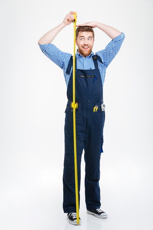 Happy funny young man in overall measuring his body height using tape