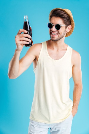 Smiling young man in hat and sunglasses standing and holding bottle of sodaの写真素材