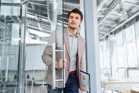 Photo pour Handsome young businessman with clipboard entering the door in office - image libre de droit