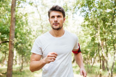 Foto de Concentrated young man athlete with handband running outdoors in the morning - Imagen libre de derechos
