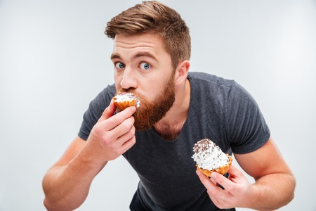 Photo pour Close up portrait of a hungry bearded man biting cream cake isolated on white background - image libre de droit