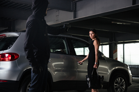 Man robber in black hoodie threatening with gun to scared businesswoman on car parking