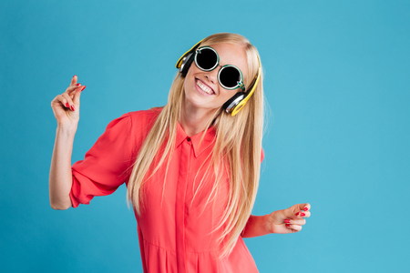 Photo pour Portrait of a smiling cheerful blonde woman in sunglasses listening music with headphones and dancing over blue background - image libre de droit