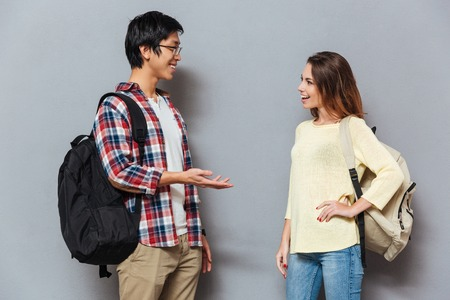 Photo pour Two young interracial students with backpacks talking isolated on the gray background - image libre de droit