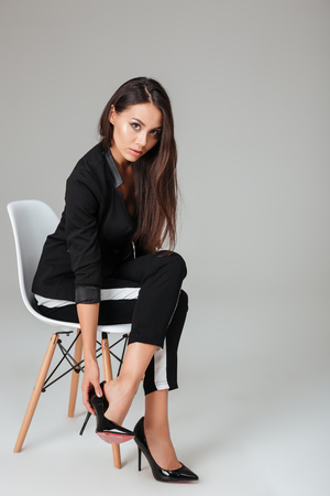 Photo for Pretty fashion model on chair looking at camera. gray background - Royalty Free Image