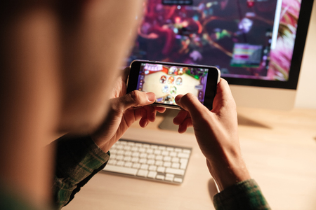 Photo pour Closeup of man playing videogame on smartphone in the evening at home - image libre de droit
