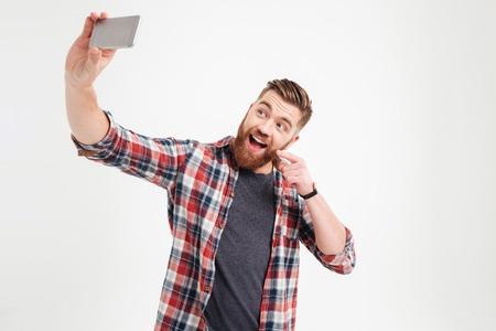 Photo pour Happy young casual man taking selfie photo over white background - image libre de droit