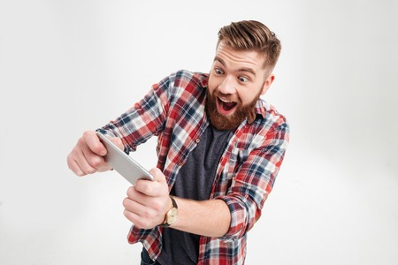 Photo pour Excited bearded man in plaid shirt playing on smartphone over white background - image libre de droit