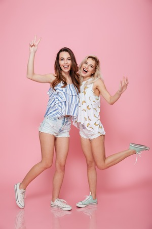 Photo pour Full length of two happy young women standing and showing peace sign over pink background - image libre de droit