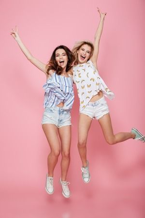 Full length of two cheerful young women showing victory sign and jumping over pink backgroundの写真素材