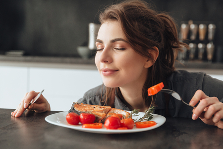 Photo pour Image of pretty young woman sitting in kitchen while eating and smells fish and tomatoes. Eyes closed. - image libre de droit