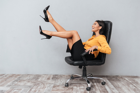 Happy cheerful business woman sitting on chair with hands up and having fun isolated over gray backgroundの写真素材