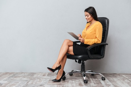 Portrait of a young business woman using tablet for work while sitting in chair isolated over gray background