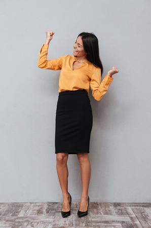 Photo pour Full length portrait of a successful happy business woman celebrating her win over gray background - image libre de droit