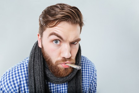 Amusing bearded young man in scarf holding thermometer in his mouth over white background