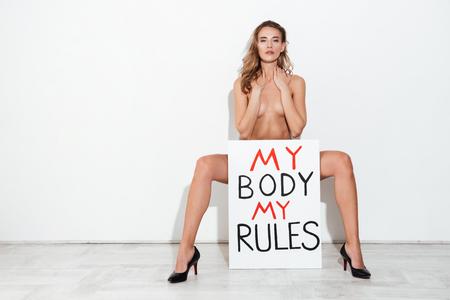 Full-length shot of naked woman feminist holding nameplate 'My body my rules'
