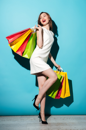 Foto de Full length portrait of a happy pretty girl holding colorful shopping bags and posing isolated over blue background - Imagen libre de derechos
