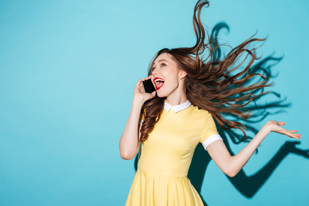 Photo pour Portrait of a happy cheerful girl with long beautiful hair wearing dress and talking on mobile phone isolated over blue background - image libre de droit